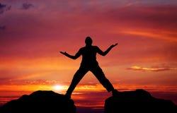 Silhouet van de mens op de achtergrond van de zonsonderganghemel Stock Afbeelding