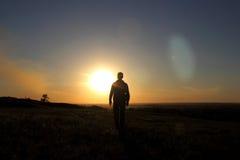 Silhouet van de mens op een gebied bij zonsondergang Royalty-vrije Stock Foto's
