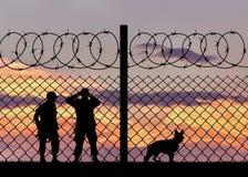 Silhouet van de militairen met een hond Stock Fotografie