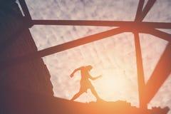 Silhouet van de moedige mens die op de bovenkant van bouw bij zonsondergang lopen stock afbeelding