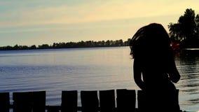Silhouet van de onbezorgde vrouw die bij het strand tijdens mooie zonsopgang dansen vakantievitaliteit gezond het leven concept