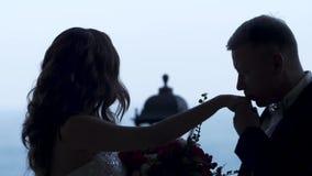 Silhouet van de paarbruidegom die de hand van de Bruid kussen overal kijkt zij doesn ` t stock video