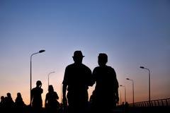Silhouet van de paarmens en vrouw die op zonsondergang lopen stock foto