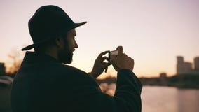 Silhouet van de reizigersmens in hoed die panoramische foto van de stadshorizon nemen op zijn smartphonecamera bij zonsondergang