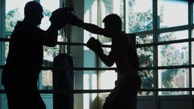 Silhouet van de trainer van de opleidende jonge bokser op een ring stock footage