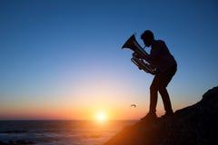 Silhouet van de Tuba van het musicusspel op overzeese kust bij verbazende zonsondergang Art royalty-vrije stock fotografie