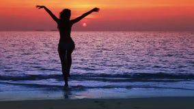Silhouet van de vrouw tegen een zonsondergang bij oceaan stock footage