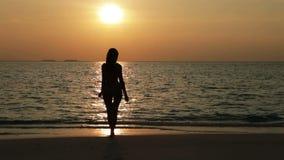 Silhouet van de vrouw tegen een zonsondergang bij oceaan stock videobeelden