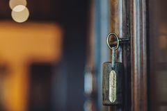 Silhouet van deursleutels die op de open deur hangen stock foto