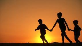 Silhouet van drie jongens die bij zonsondergang runniing stock video