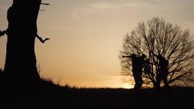 Silhouet van drie mensen die pret en het dansen hebben Zij spelen de gitaar en zingen liederen Langzame Motie stock video