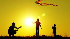 Silhouet van drie onherkenbare mensen De gelukkige jonge geitjes en de vader spelen met een vlieger bij zonsondergang Onderwijs e stock video