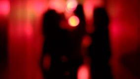 Silhouet van drie sexy vrouwen die in een onscherpe, rode gang met haar opgeheven handen dansen stock videobeelden