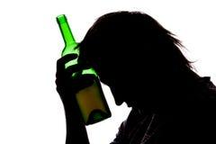 Silhouet van droevige mens het drinken alcohol stock afbeelding