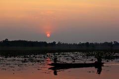 Silhouet van een boot in het reservoir En zonsondergang stock foto
