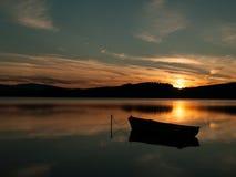 Silhouet van een boot op een meer met zonsondergang Royalty-vrije Stock Afbeelding