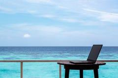 Silhouet van een computer op een lijst Duidelijk blauw tropisch water als achtergrond stock fotografie