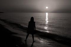 Silhouet van een dame die door het overzees lopen royalty-vrije stock afbeelding