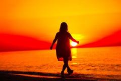 Silhouet van een dame die door het overzees lopen stock foto