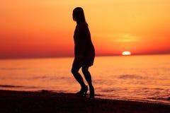 Silhouet van een dame die op het strand dansen Stock Foto's
