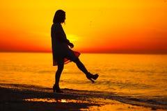 Silhouet van een dame die op het strand dansen stock afbeeldingen