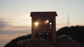Silhouet van een document huis in handen bij zonsondergang in de zon stock footage