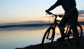 Silhouet van een fietser bij zonsondergang Stock Foto's