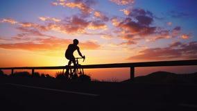 Silhouet van een fietser bij zonsondergang in de bergen stock videobeelden
