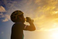 Silhouet van een fietsermannetje die een water na het berijden van roa drinken stock fotografie