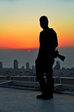 Silhouet van een fotograaf in de zonsondergang van een wolkenkrabber Royalty-vrije Stock Afbeelding
