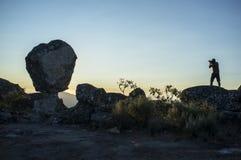 Silhouet van een fotograaf die zon schieten die boven het onderstel toenemen Royalty-vrije Stock Foto's