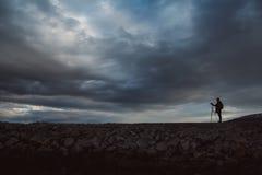 Silhouet van een fotograaf of een reiziger met driepoot die zich op steen bevinden Achtergrond van een dramatische hemel Het geva stock foto's