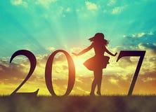 Silhouet van een gelukkig meisje die in viering van het Nieuwjaar 2017 dansen Stock Afbeeldingen