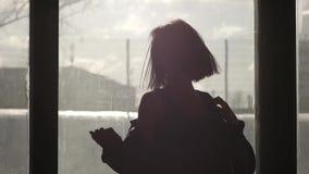 Silhouet van een gelukkig meisje die voor een venster dansen stock video