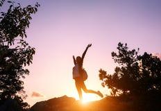 Silhouet van een gelukkige jonge vrouw in bergen bij zonsondergang stock foto