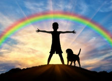 Silhouet van een gelukkige kind en een hond stock foto