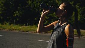 Silhouet van een gelukkige vrouwelijke fietser die haar fiets en drinkwater berijden stock footage