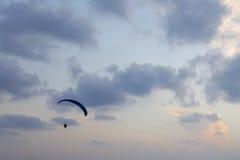 Silhouet van een glijscherm in de avond hemel die over het overzees hangen Stock Fotografie