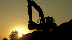 Silhouet van een graafwerktuig dat zand in een vrachtwagen bij zonsondergang laadt De conceptenbouw en de zware industrie, machin stock video