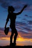 Silhouet van een haar hoed houden en veedrijfster die omhoog bereiken Stock Afbeeldingen