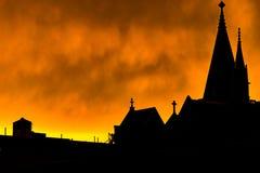 Silhouet van een Harlem-dak, schoorstenen, en kerktorenspitsen, tegen een heldere gele vurig-kijkt hemel tijdens zonsondergang royalty-vrije stock afbeelding