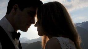 Silhouet van een houdend van paar op de achtergrond van de het plaatsen zon, bergen stock footage