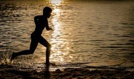 Silhouet van een Jong geitje die over een Surfplank lopen Royalty-vrije Stock Afbeeldingen