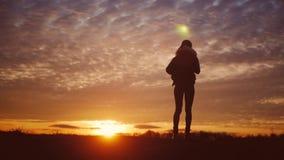 Silhouet van een jong gelukkig meisje met een rugzak die haar handen omhoog houden de sportvrouw Het toejuichen van succesvolle v stock videobeelden