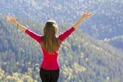 Silhouet van een jong gelukkig mooi slank meisje in rode sweater die zich op grote rotsen in bergen bevinden die handen opheffen  Stock Foto's