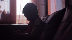 Silhouet van een jong jongens speelspel op smartphone in huis stock footage