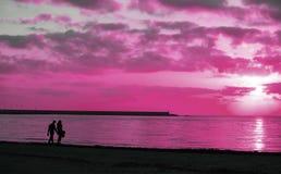 Silhouet van een jong paar die door het overzees lopen royalty-vrije stock fotografie