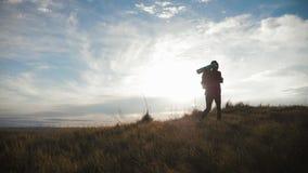 Silhouet van een jong wandelaarmeisje met een rugzak op hoogste bergen bij zonsondergang stock videobeelden