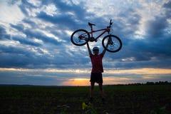 Silhouet van een jonge mens die een fiets op het gebied houden bij zonsondergang met een dramatische hemel royalty-vrije stock fotografie