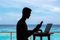 Silhouet van een jonge mens die met een computer en een smartphone aan een lijst werken Duidelijk blauw tropisch water als achter stock foto